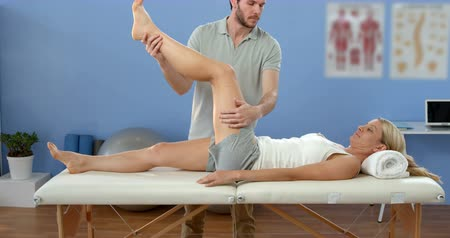 fizjoterapeuta : Female patient receiving leg massage from physiotherapist in clinic Wideo