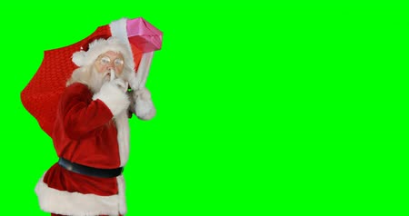 santa : Santa claus carrying gifts in sack during christmas time on green background 4k Stock Footage