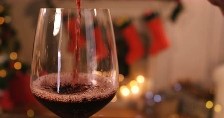 kırmızı şarap : Red wine pouring into glass on wooden table during christmas time 4k