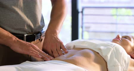 gyomor : Physiotherapist giving stomach massage to a female patient in clinic 4k