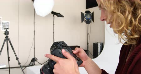 filmagens : Photographer looking at photos on digital camera in studio 4k