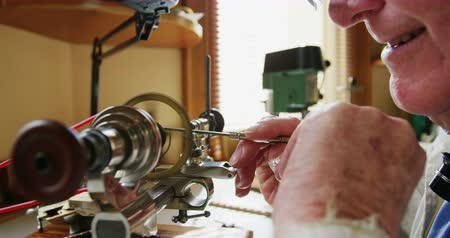 instrument maker : Horologist using a machine in the workshop