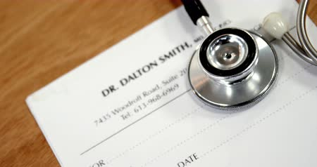 papier firmowy : Close-up of paper with stethoscope on table Wideo