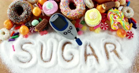 диабет : Various types of doughnuts and cupcakes with glucometer on wooden table