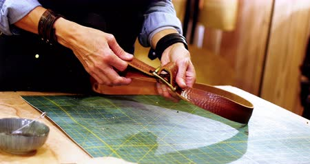 couro : Mid section of craftswoman making leather belt in workshop
