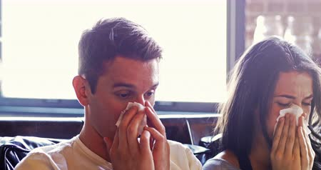 foukání : Ill couple rubbing their nose with tissue paper in living room Dostupné videozáznamy