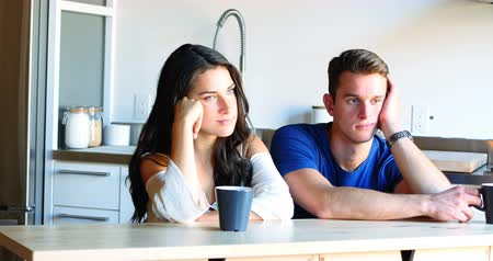 gondolkodás : Thoughtful couple sitting in kitchen at home
