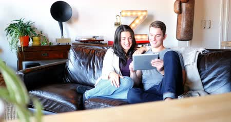 czytanie : Couple using digital tablet in living room at home