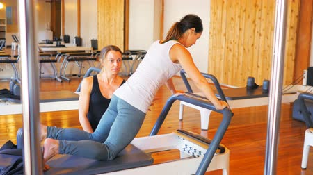 тренер : Female trainer assisting woman with exercise in fitness studio