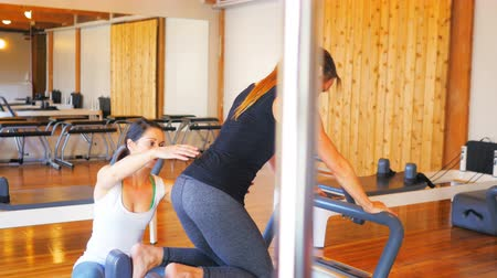 trener : Female trainer assisting woman with exercise in fitness studio