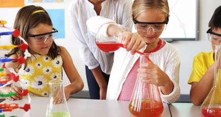 uczenie się : School kids doing a chemical experiment in laboratory at school