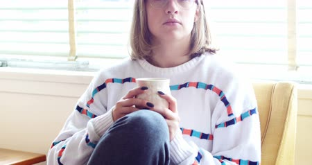 háztartás : Thoughtful woman having cup of coffee in living room at home Stock mozgókép