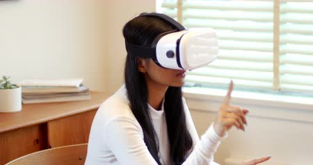 fejhallgató : Woman using virtual reality headset in living room at home
