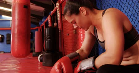 confiança : Tired female boxer sitting in the ring in fitness studio