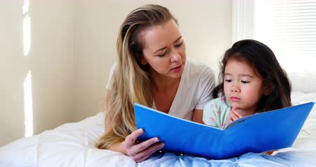 bonding : Mother and daughter reading book on bed in bedroom Stock Footage