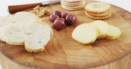 cálcio : Slices of bread, crackers, olives, walnut and knife on wooden board against white background Vídeos