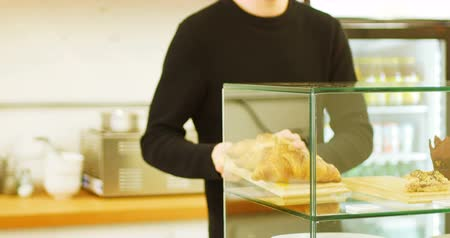 bandeja : Mid section of man keeping tray of croissants in display case of coffee shop