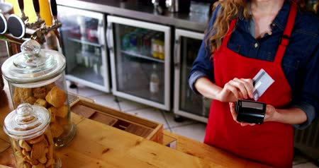 counter : Waitress swiping credit card at counter in café