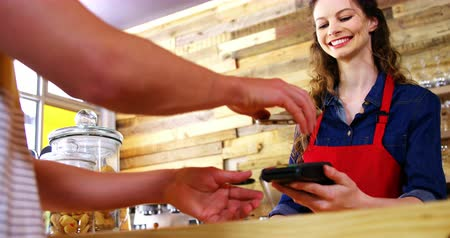 banknoty : Costumer paying bill through smartphone using NFC technology in café