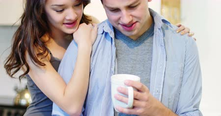 bonding : Couple interacting while having coffee in living room at home Stock Footage
