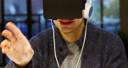 fejhallgató : Smiling man using virtual reality headset at home