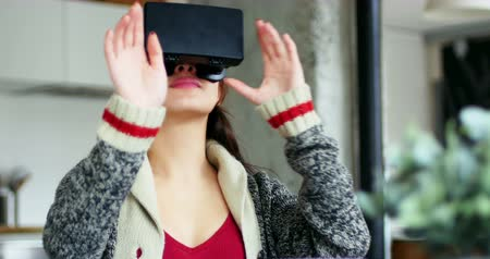fejhallgató : Smiling woman using virtual reality headset at home Stock mozgókép