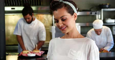 garçonete : Happy waitress standing in kitchen at restaurant