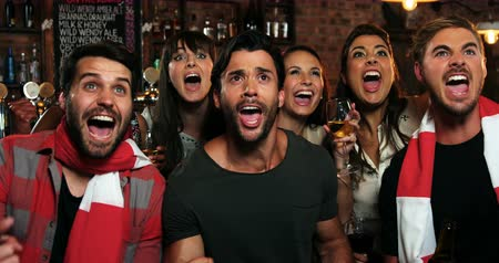 excitação : Group of friends watching tv and cheering in bar