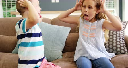 tongue out : Boy and girl sitting on sofa teasing each other in living room