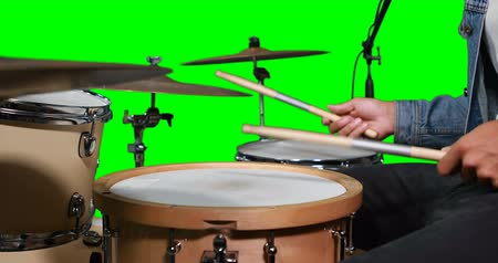perkusja : Mid section of drummer playing drum against green screen