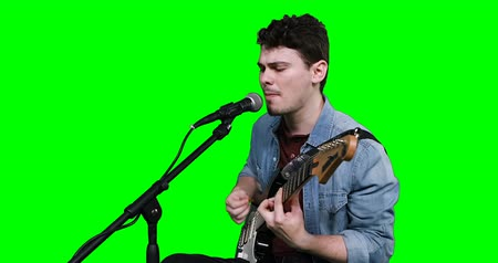 śpiew : Male musician singing while playing guitar against green screen