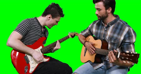 electric : Male musicians playing guitar against green screen