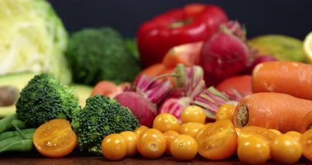 halve : Variety of fresh vegetables and fruits on wooden table Stock Footage