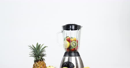 halve : Various fruits and vegetables in blender on wooden table