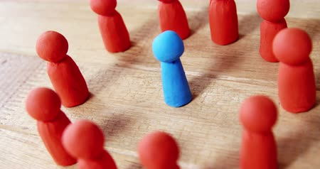 reconcile : Conceptual image of blue figurine standing between a group of red figurines Stock Footage