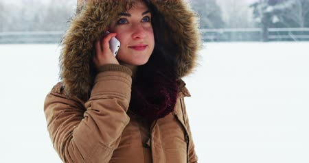 kürk : Smiling woman in fur jacket talking on mobile phone during snowfall