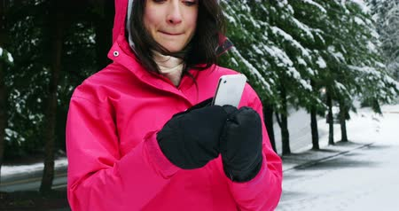 télen : Smiling woman in warm clothing using mobile phone during snowfall Stock mozgókép