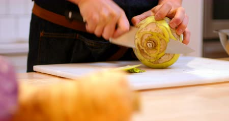 kávézó : Mid section chef chopping the outer skin of kohlrabi vegetable