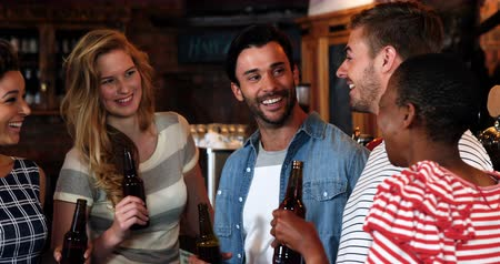 дружба : Smiling group of friends interacting while having bottle of beer in pub Стоковые видеозаписи