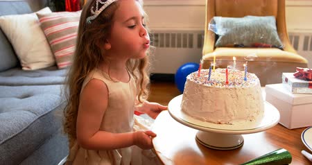 ajándékdobozban : Girl blowing candles on birthday cake at home Stock mozgókép