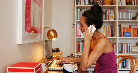 kufel : Beautiful woman talking on mobile phone while using laptop at home
