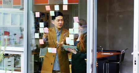 yapışkan : Business executives discussing over sticky notes in office