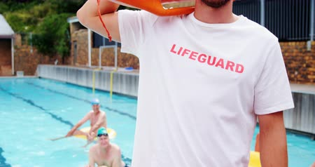 bóia : Portrait of swim coach standing inflatable floater near poolside
