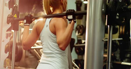 súlyzó : Fit woman exercising with smith machine in gym Stock mozgókép