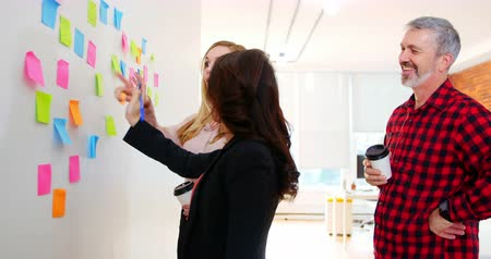 parede : Executives discussing over sticky notes in office Vídeos