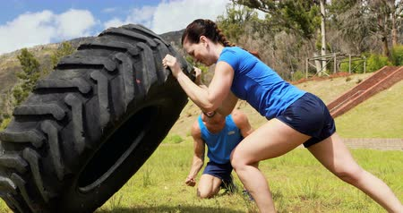 csizma : Male trainer giving training to woman during obstacle course in boot camp
