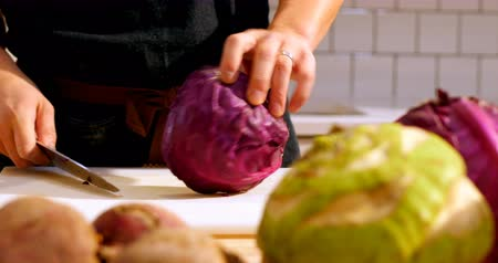 bıçak : Mid section of chef cutting purple cabbage in cafe kitchen Stok Video