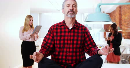 pozisyon : Male executive performing yoga while his executive standing in background at office