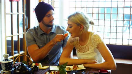 feed on : Man feeding sushi to woman in restaurant Stock Footage