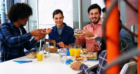 sandviç : Happy executives interacting while having breakfast in office Stok Video